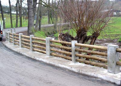 Barriere aus Rundholz zwischen Betonstehlen